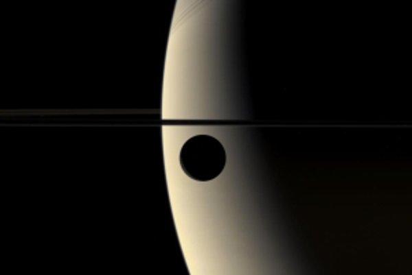 Rhea na pozadí Saturna.
