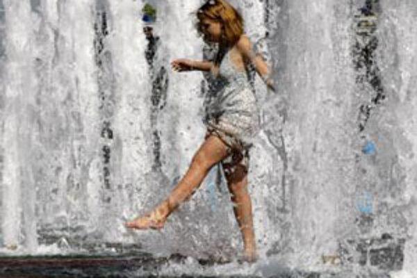 Mladá žena sa osviežuje vo fontáne 21. mája 2010 v Moskve. Teploty v meste sa vyšplhali na 25 stupňov, čo bolo nezvyčajné pre májové dni.
