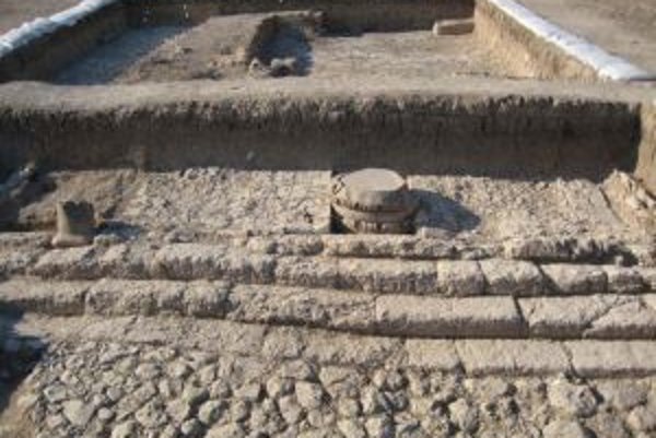 Vydláždené nádvorie a schodisko na južnej strane chrámu v Tell Tayinat. Vpravo od stredu je základ zdobeného stĺpu, vľavo od schodiska zvyšok malého stĺpu.