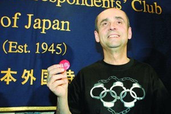 Šéf organizácie Reportéri bez hraníc Robert Menard drží odznak  s nápisom Sloboda v čínštine.