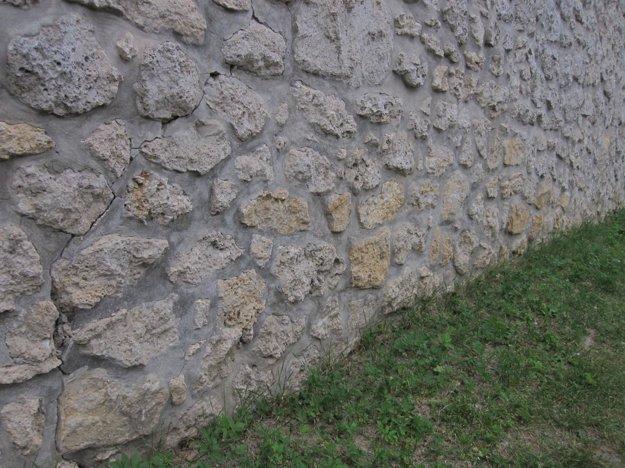 Veľké praskliny sa tiahnu hradným múrom.