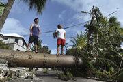 Muži stoja na strome,ktorý spadol počas hurikánu Humberto. Hamilton, Bermuda, 19. september 2019.