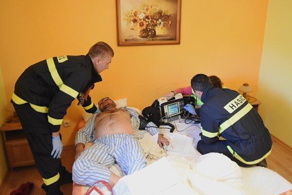 Záchranársky tím hasičov vyšetruje pacienta s početnými ťažkosťami.