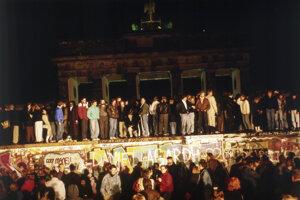 Na snímke z 10.novembra 1989 Berlínčania z východnej a západnej časti mesta stoja na a pri Berlínskom múre pred Brandenburskou bránou.