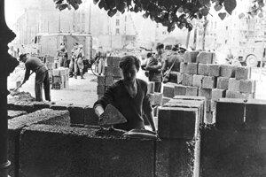 Na archívnej fotografii z 13. augusta 1961 robotník stavia časť múru medzi východnou a západnou časťou Berlína.