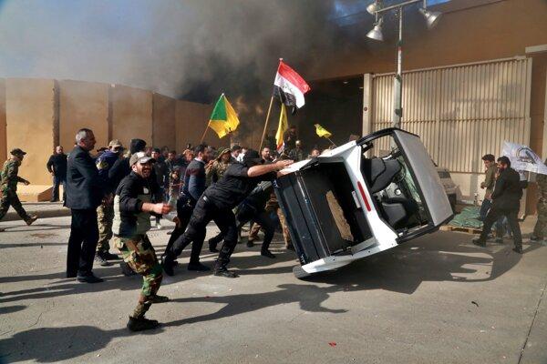 Protestujúci poškodzujú majetok pred budovou amerického veľvyslanectva v Bagdade 31. decembra 2019.