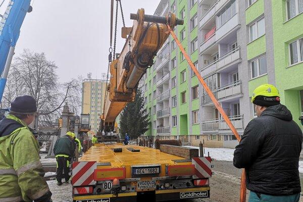 Nakladanie ramena demolačného stroja na príves.