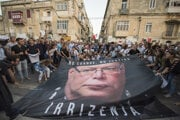 Ľudia kladú na zem plagát s portrétom maltského policajného komisára Lawrencea Cutajara pred sídlom maltskej polície počas protestného zhromaždenia na uctenie pamiatky maltskej investigatívnej novinárky Daphne Caruanovej Galiziovej po jej tragickej smrti vo Vallette na Malte 22. októbra 2017.