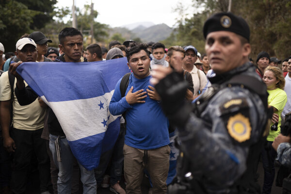 Migranti z Hondurasu a guatemalský policajt. Agua Caliente, Guatemala, 16. január 2020.