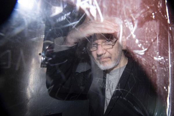 Julian Assange vo väzenskom transporte.