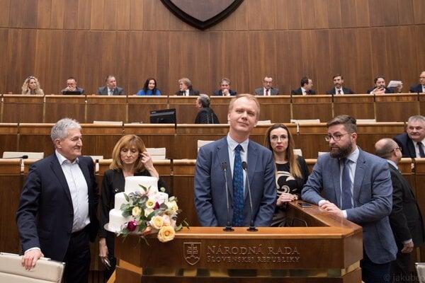 Poslanci koalície PS/Spolu sa postavili k rečníckemu pultu s tortou, ktorá má podľa nich symbolizovať spoluprácu Smeru s ĽSNS.