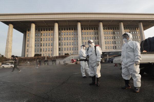 Pracovníci v špeciálnych ochranných odevoch dezinfikujú priestor pred budovou parlamentu v Soule v pondelok 24. februára 2020.