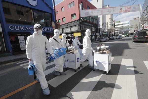 Pracovníci v ochranných odevoch používajú spreje s dezinfekčnými roztokmi proti koronavírusom.