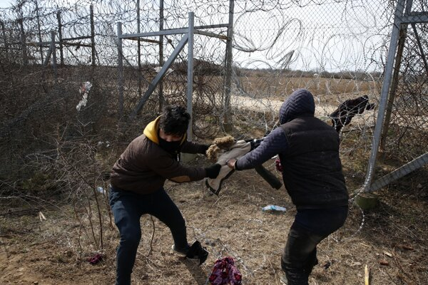 Migranti sa pokúšajú prerezať oplotenie s ostnatým drôtom počas zrážok s príslušníkmi gréckej poriadkovej polície v dedine Edirne na turecko-gréckej hranici Pazarakule 2. marca 2020.