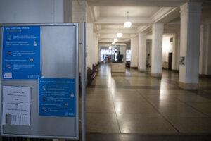 Prázdna chodba s plagátmi o upozorneniach na nový koronavírus v areáli Univerzity Komenského.