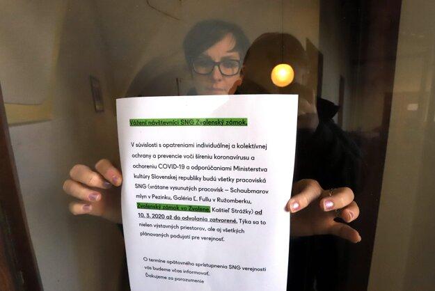 Riaditeľka Slovenskej národnej galérie Erika Trnková lepí oznam o uzavretí galérie na Zvolenskom zámku vo Zvolene.