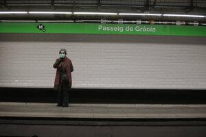 Osamelá cestujúca s rúškom na tvári stojí na nástupišti na vlakovej stanici v Barcelone.