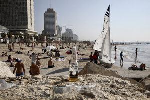 Izraelčania sa opaľujú na pláži v Tel Avive. Izraelská vláda nariadila pre šíriaci sa nový koronavírus zatvorenie reštaurácií, obchodných domov, kín, telocviční a denných centier.