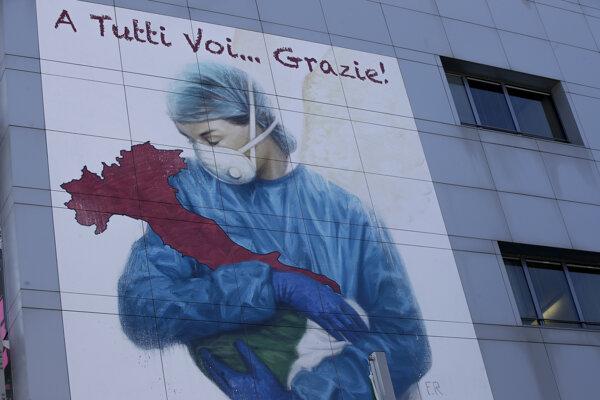 """Kresba v nadrozmernej veľkosti zobrazuje zdravotnú pracovníčku s ochranným rúškom na tvári objímajúcu čižmu v tvare Talianska a nápis """"Ďakujeme vám všetkým"""". Nachádza sa na budove nemocnice v severotalianskom meste Brescia."""