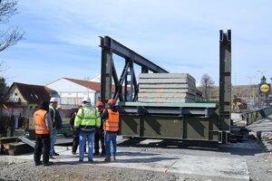 Robotníci na stavbe dočasného mosta cez rieku Poprad v Kežmarku.