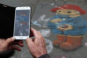 Turista si fotografuje na chodníku maľbu medvedíka Paddington s ochranným rúškom a dezinfekčným gélom na ruky v Londýne.