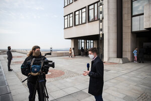 Novinári pred kamerami vystupujú s ochrannými rúškami.