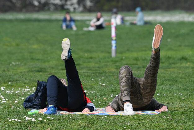 Dvojica cvičí na tráve v parku v nemeckom meste Frankfurt.