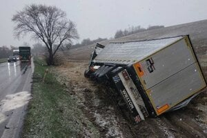 Kamión s návesom po nehode skončil prevrátený v poli.