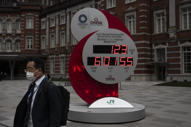 estujúci kráča okolo hodín, ktoré odpočítavajú dni do začiatku tohtoročných letných olympijských hier v Tokiu.