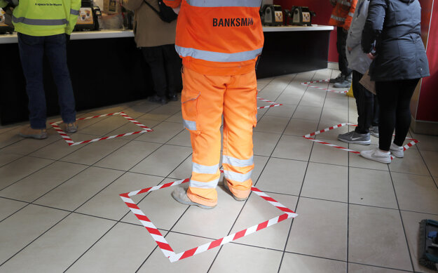 Zákazníci stoja na vyznačených štvorcoch, aby zachovali dostatočný vzájomný odstup v reštaurácii s rýchlym občerstvením v Londýne.