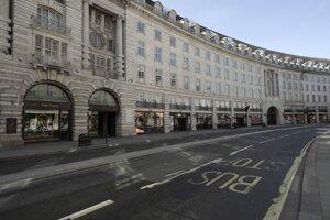 Osamelý cestujúci čaká na autobusovej zastávke na prázdnej ulici Regent Street v Londýne.