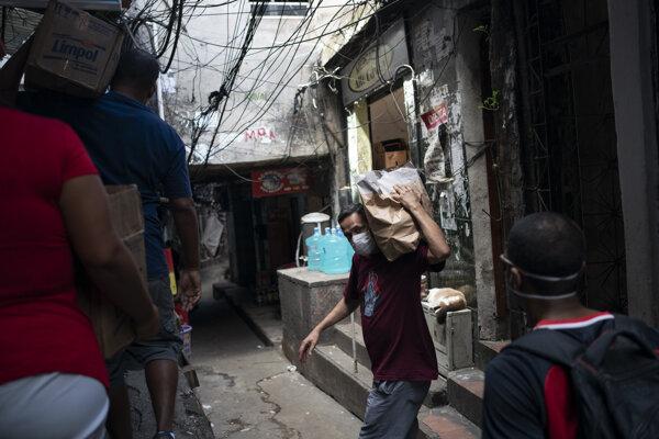 Muž nesie balík s mydlom vo favele Rocinha v Riu de Janeiro.