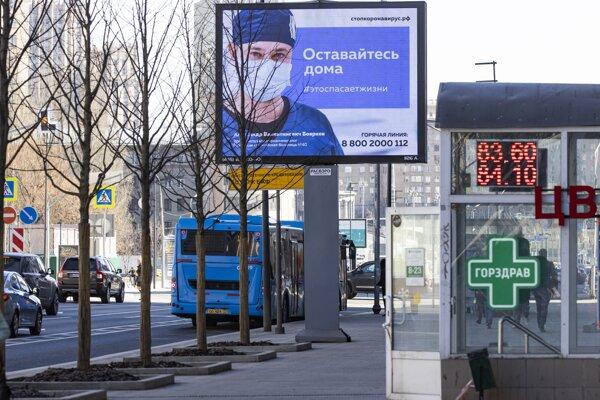 """Elektronický billboard na ulici v Moskve zobrazujúci lekára s rúškom so slovami """"Zostaňte doma, zachráni život""""."""