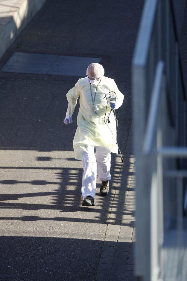 Zdravotník v ochrannom obleku beží na vlakovom nástupišti počas evakuácie pacientov s Covid-19 do intenzívnej starostlivosti z vysokorýchlostného vlaku na železničnej stanici v Štrasburgu.