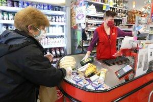Zákazníčka nakupuje s ochrannými rukavicami.