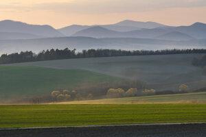 Pohľad z rozhľadne na okolitú poľnohospodársku krajinu, v pozadí pohorie Čierna hora.