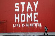 Žena s rúškom prechádza okolo nápisu Zostaňte doma, život je krásny v Los Angeles.