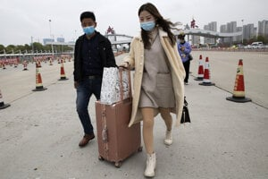 Žena kráča na okraji čínskeho mesta Wu-chan.