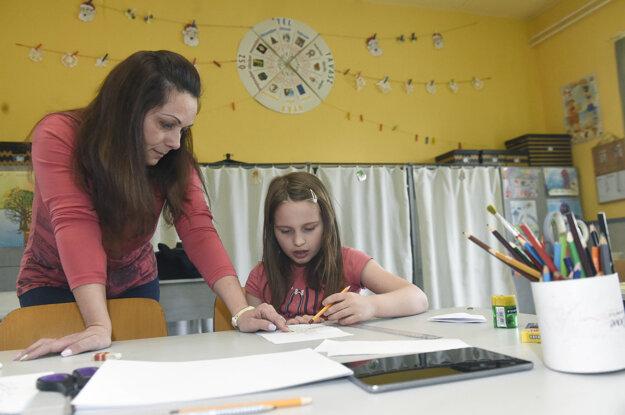 Asistentka učiteľa pomáha žiačke s úlohami a učivom v škole v Budapešti.