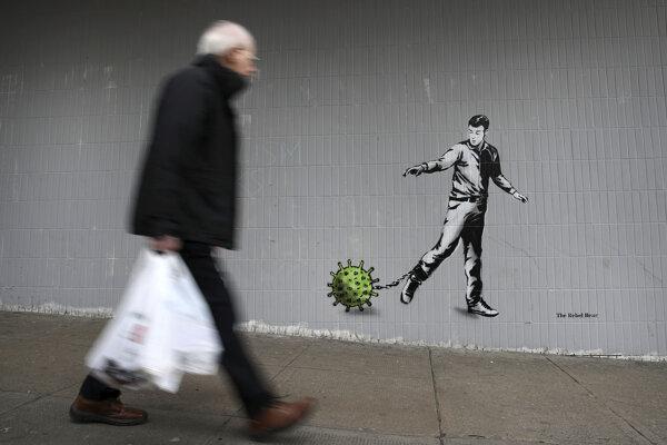 Muž prechádza okolo nástennej maľby na tému koronavírusu na Bath Street v Glasgowe.