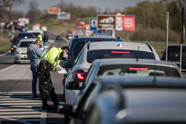 Kontrolné stanovište Polície SR na hlavnej ceste v smere do Stupavy počas mimoriadnej situácie.