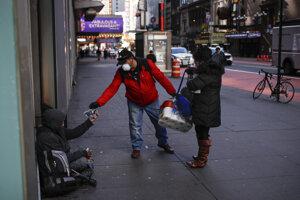 Pár v New Yorku podáva peniaze bezdomovcovi.