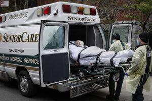 Zdravotníci nakladajú pacienta s ochorením COVID-19 do sanitky pred nemocnicou v newyorskej štvrti Brooklyn.