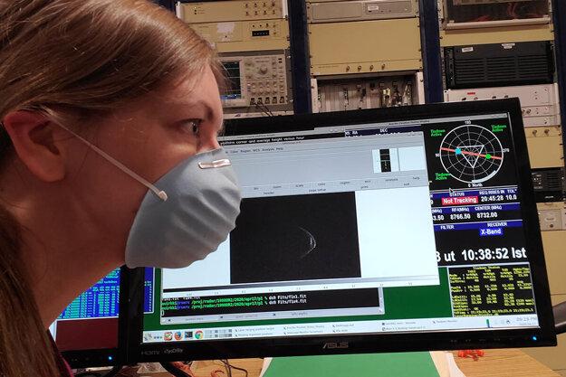 Astronómka Anne Virkkiová s maskou. V pozadí na obrazovke asteroid 1998 OR2.