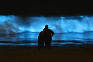 Ľudia sledujú vlny sfarbené do modra od morských rias vo vodách Tichého oceánu.