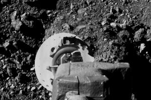 Záber na rameno sondy OSIRIS-REx, v ktorom je nástroj na odber vzorky povrchu asteroidu Bennu.