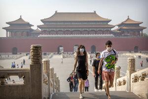 Návštevníci s ochrannými rúškami kráčajú v palácovom komplexe Zakázané mesto v Pekingu.