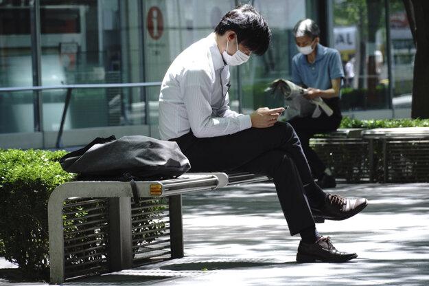 Koronavírus v Japonsku: Muž s ochranným rúškom oddychuje na lavičke 14. mája 2020 v Tokiu.