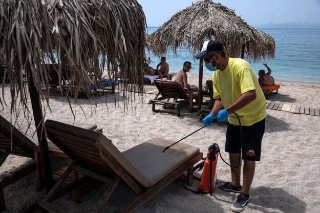 Zamestnanec dezinfikuje ležadlá na pláži v Alimose blízko Atén. Grécko opäť sprístupnilo verejné pláže, no pod prísnymi bezpečnostnými nariadeniami v dôsledku pandémie koronavírusu.