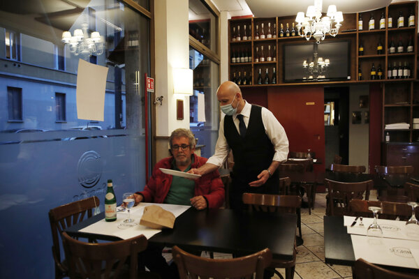 Čašník obsluhuje zákazníka v reštaurácii.